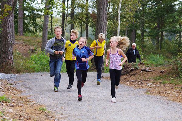 Barn joggar i skogen