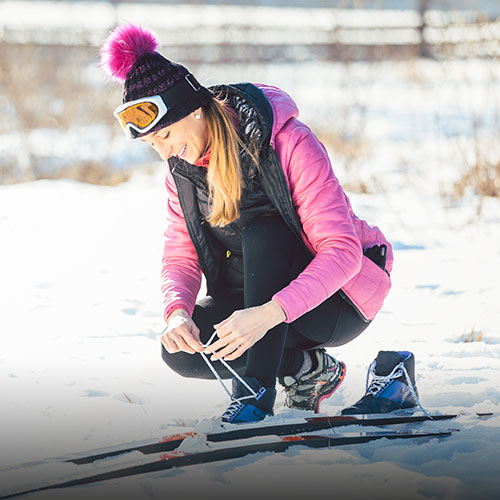 Woman cross country skier putting on ski