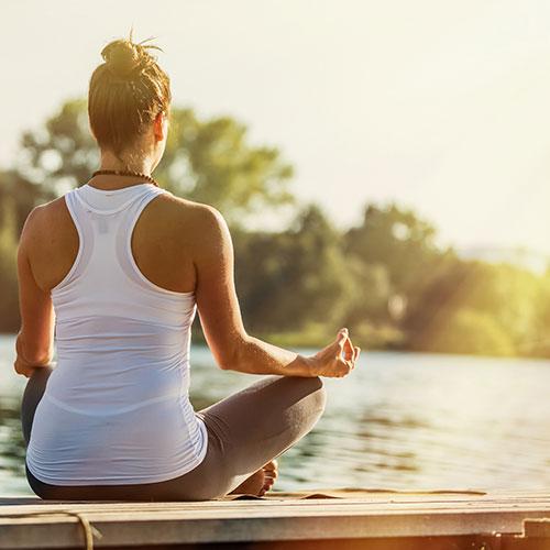 tjej mediterar på brygga