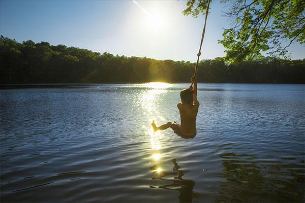 Pojke i lian ovanför vattnet